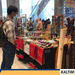 Salah satu pengunjung yang sedang melihat kerajinan khas Kalimantan Timur.